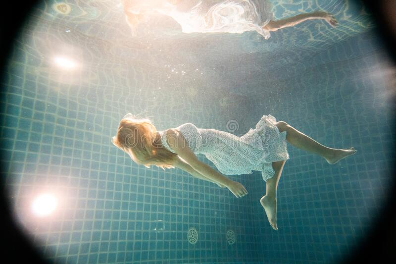 Linda mulher posando debaixo d'água de vestido branco fotos de stock royalty free