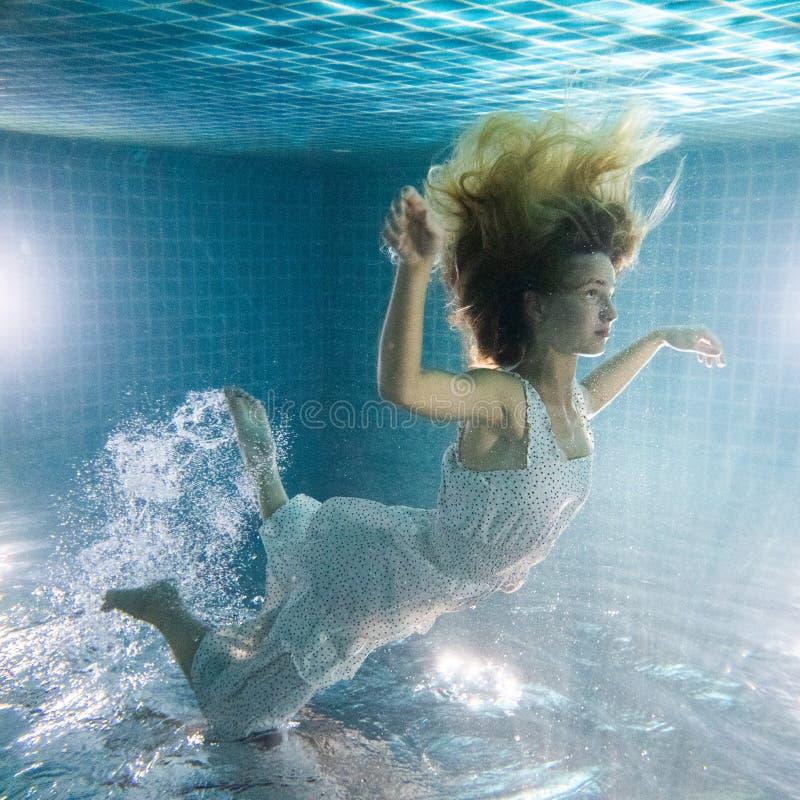 Linda mulher posando debaixo d'água de vestido branco imagens de stock royalty free