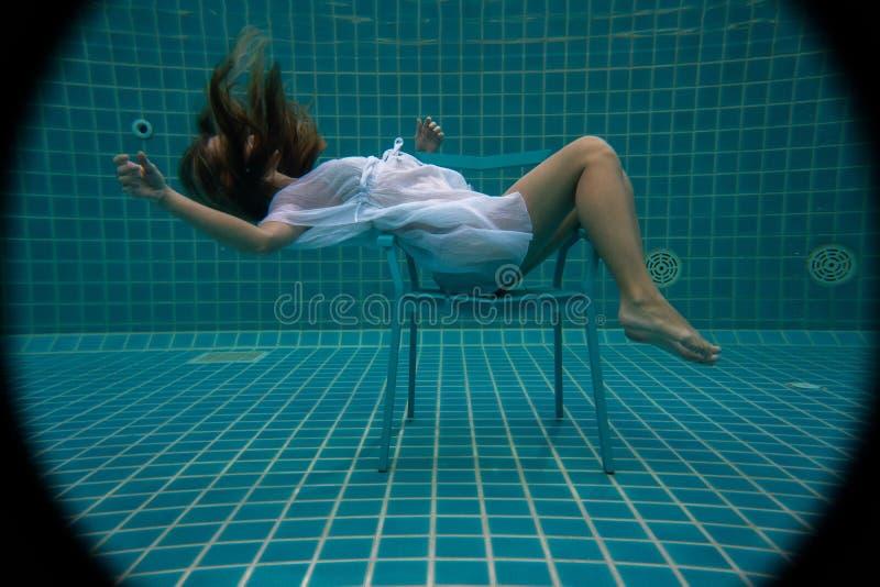 Linda mulher se posando debaixo d'água na cadeira fotografia de stock royalty free