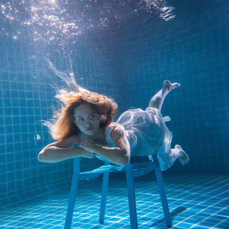 Linda mulher se posando debaixo d'água na cadeira de vestido branco imagem de stock