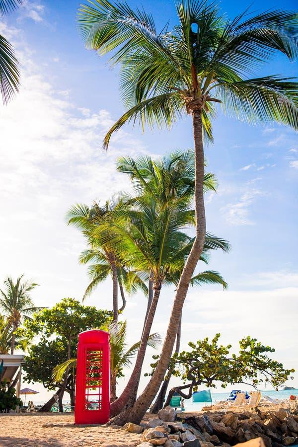 Linda paisagem com uma cabine telefônica clássica na praia branca arenosa em Antígua fotografia de stock royalty free