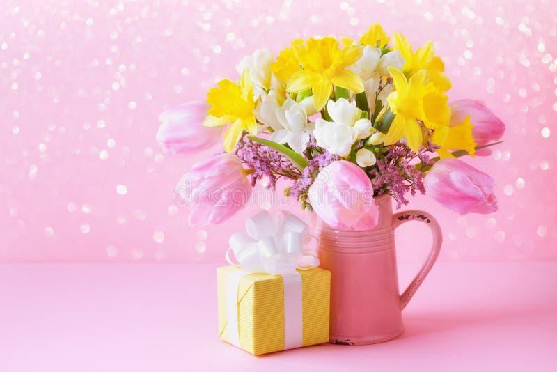 Lindas flores de primavera em vaso e presente contra fundo rosa Cartão de saudação do dia das mães ou das mulheres fotografia de stock royalty free