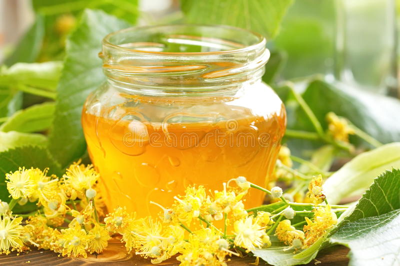 Linden honey in glass jar stock photos