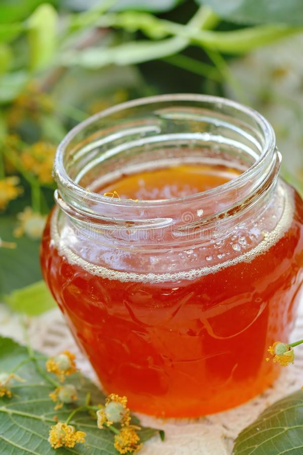 Linden honey in glass jar. And linden flowers stock photos