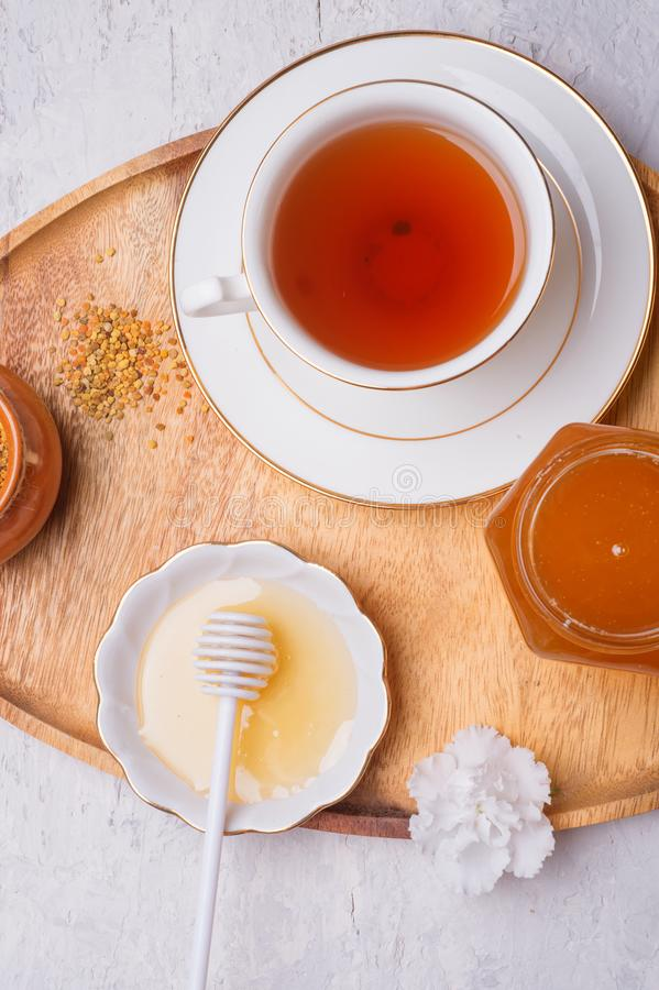 Linden honey with perga and cup of tea at wooden tray at white table.  flat lay stock photography