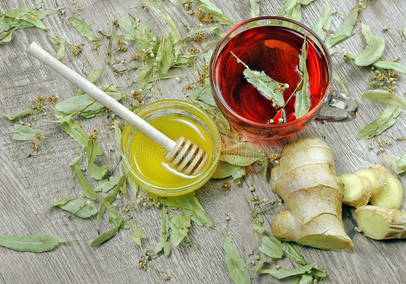 Linden tea on wooden table. a cup of linden tea, honey and ginger top view. traditional remedies for colds and flu. Linden tea on wooden table. a cup of linden royalty free stock photos
