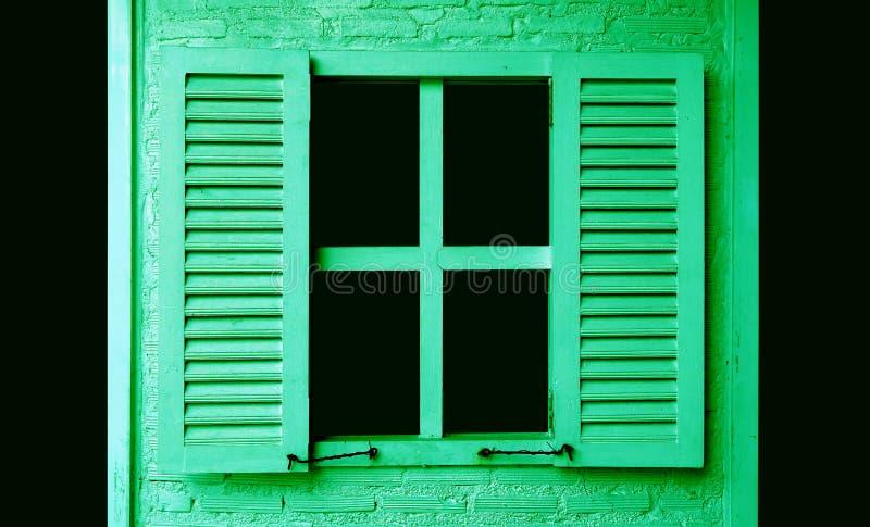 Lindgrün farbiges hölzernes Fenster mit Fensterläden auf grüner Backsteinmauer stockbilder
