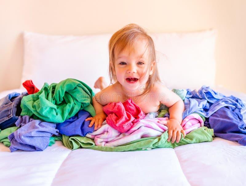 Lindo, adorable, sonriendo, beb? cauc?sico que se sienta en una pila de lavadero sucio en cama fotos de archivo libres de regalías