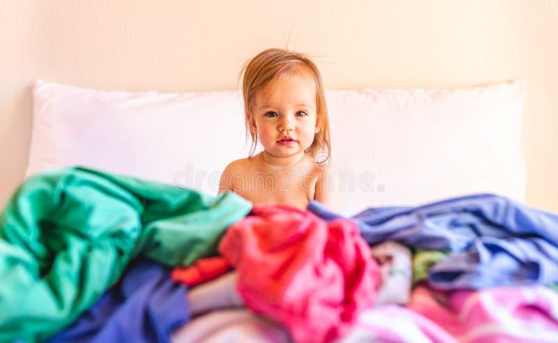 Lindo, adorable, sonriendo, beb? cauc?sico que se sienta en una pila de lavadero sucio en cama imagen de archivo