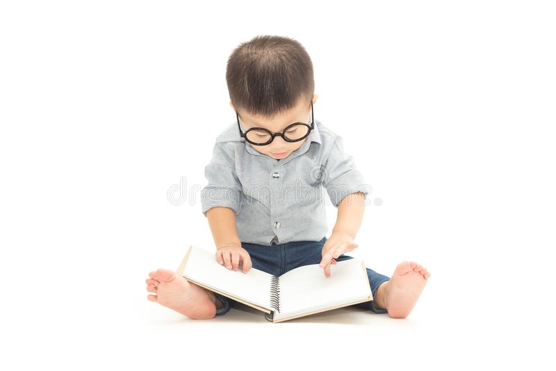 Lindo poco juego de niños con el libro y los vidrios que llevan mientras que se sienta en piso sobre el fondo blanco foto de archivo