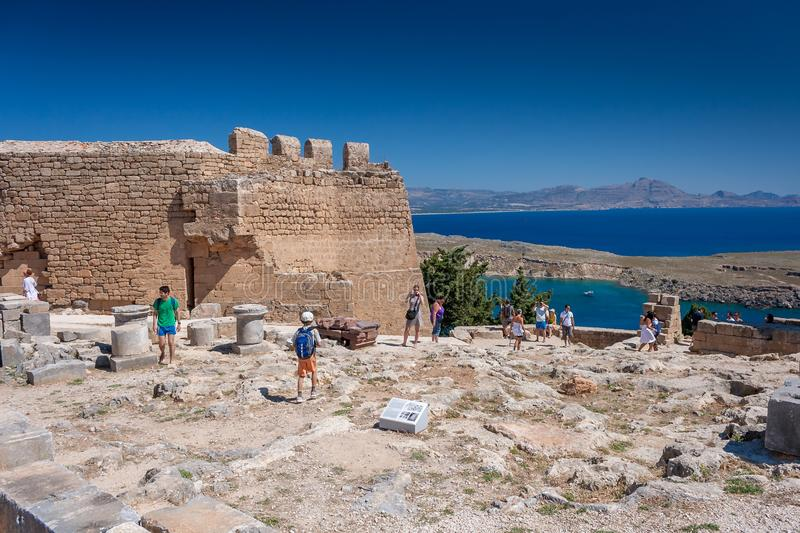 LINDOS GREECE 7 JUNE 2012: s, Greece. Tourists visit the ruins of an ancient castle in Lindos, Greece. LINDOS, GREECE 7 JUNE 2012: s, Greece. Tourists visit the royalty free stock images