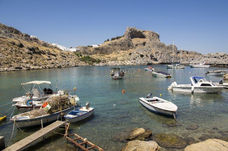 Lindos, o Rodes/GRÉCIA - 7 de setembro de 2018: Uma das praias as mais surpreendentes no Rodes com barcos, sunbeds e guarda-sóis imagem de stock royalty free