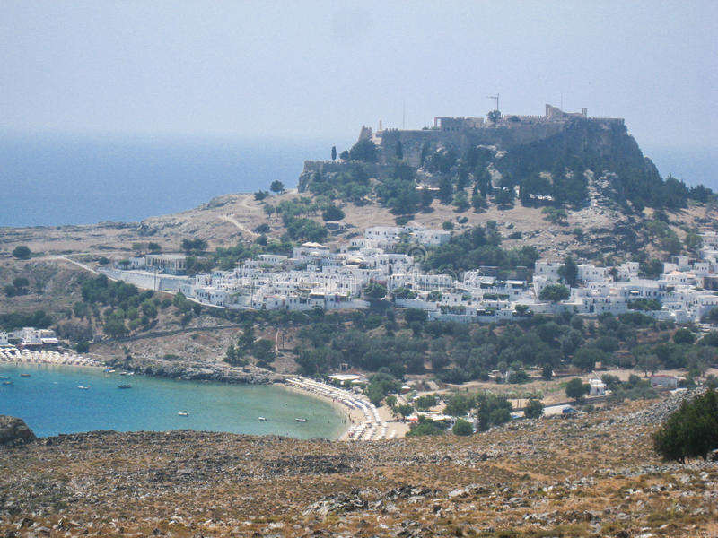 Lindos Rhodes Greece. The blue waters of the beach, the typical white greek housing of the town climbing the hill and the imposing Knights fortress on its top stock photos