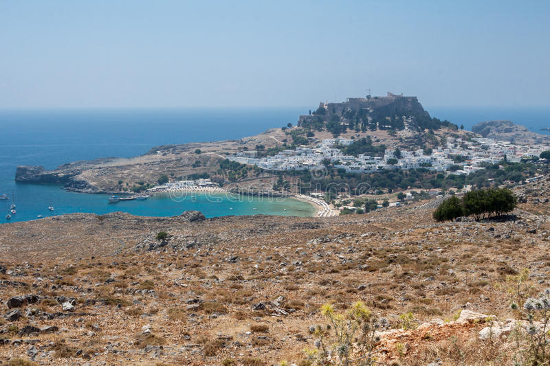 Lindos Rhodes Greece. The blue waters of the beach, the typical white greek housing of the town climbing the hill and the imposing Knights fortress on its top stock images