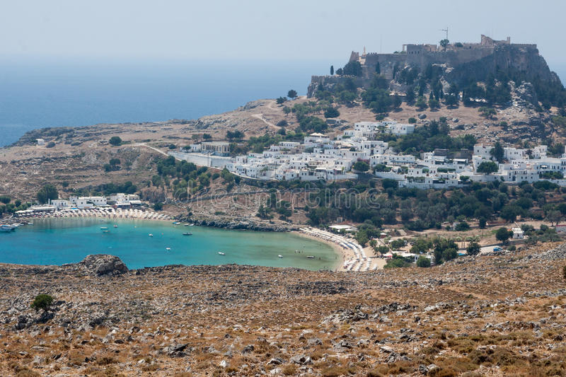 Lindos Rhodes Greece. The blue waters of the beach, the typical white greek housing of the town climbing the hill and the imposing Knights fortress on its top royalty free stock photo
