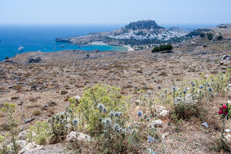 Lindos Rhodes Greece. The blue waters of the beach, the typical white greek housing of the town climbing the hill and the imposing Knights fortress on its top royalty free stock image