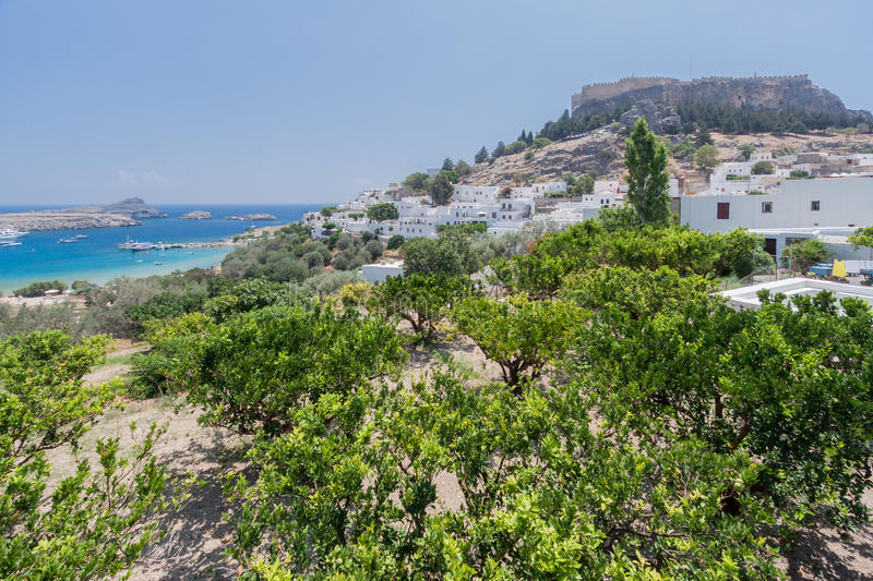 Lindos Rhodes Greece. The blue waters of the beach, the typical white greek housing of the town climbing the hill and the imposing Knights fortress on its top royalty free stock photography