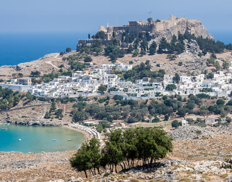 Lindos Rhodes Greece. The blue waters of the beach, the typical white greek housing of the town climbing the hill and the imposing Knights fortress on its top stock image