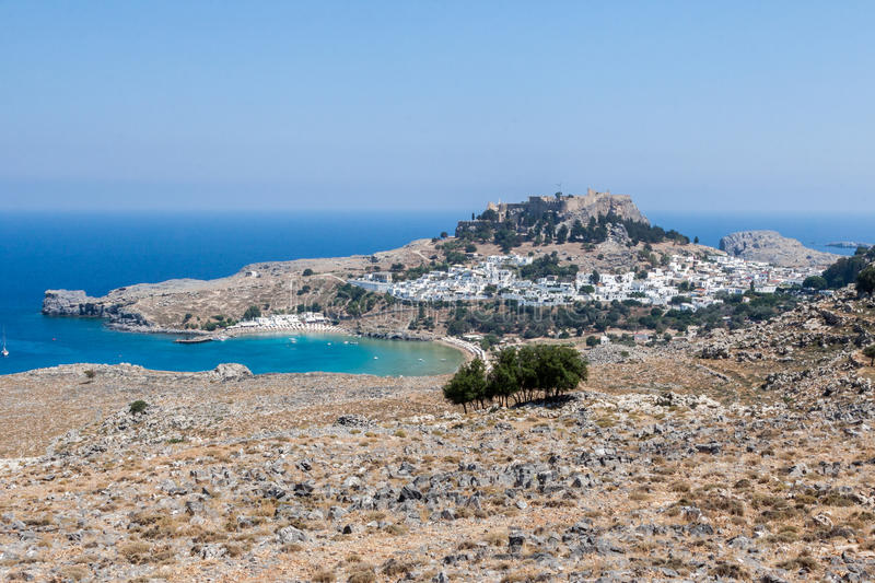 Lindos Rhodes Greece. The blue waters of the beach, the typical white greek housing of the town climbing the hill and the imposing Knights fortress on its top royalty free stock photos