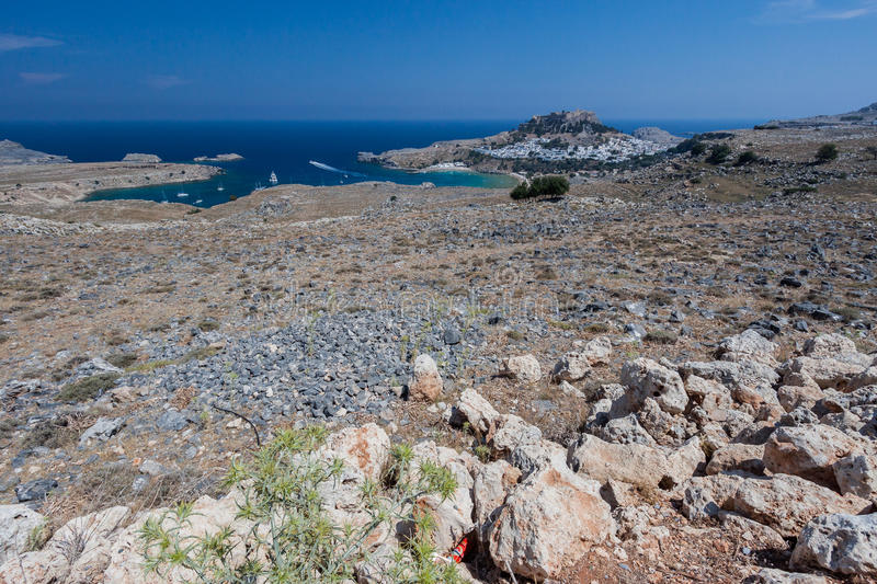 Lindos Rhodes Greece. The blue waters of the beach, the typical white greek housing of the town climbing the hill and the imposing Knights fortress on its top stock photography
