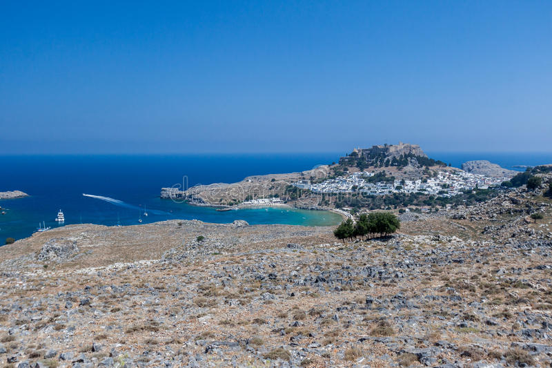 Lindos Rhodes Greece. The blue waters of the beach, the typical white greek housing of the town climbing the hill and the imposing Knights fortress on its top royalty free stock images