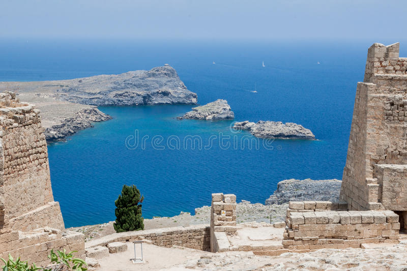 Lindos Rhodes Greece. The blue waters and the imposing Knights fortress on its top. Lindos, Rhodes Island, Greece royalty free stock photos