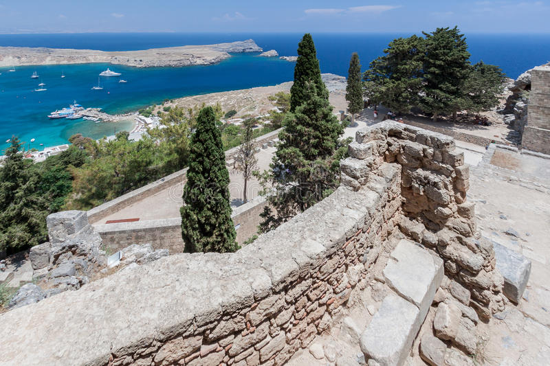 Lindos Rhodes Greece. The blue waters and the imposing Knights fortress on its top. Lindos, Rhodes Island, Greece royalty free stock photo