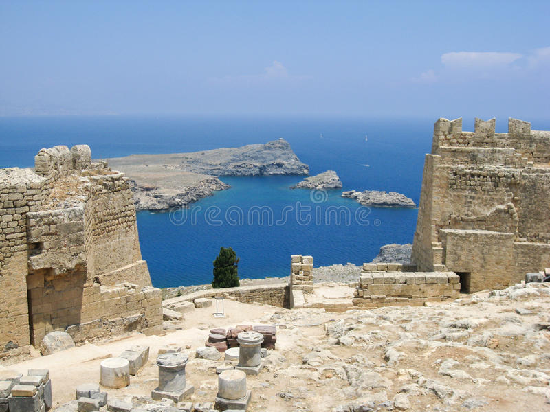 Lindos Rhodes Greece. The blue waters and the imposing Knights fortress on its top with the ruins of the ancient greek Athena temple columns. Lindos, Rhodes royalty free stock photos