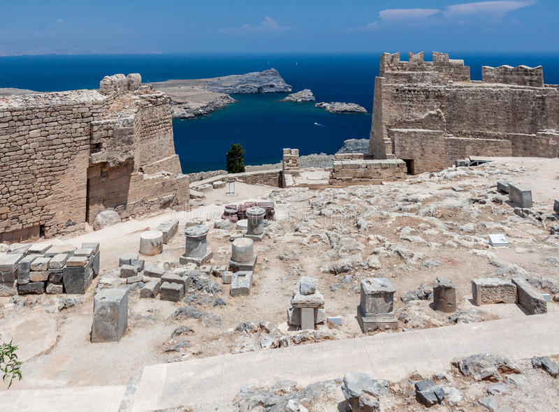 Lindos Rhodes Greece. The blue waters and the imposing Knights fortress on its top with the ruins of the ancient greek Athena templ. Lindos, Rhodes Island royalty free stock image