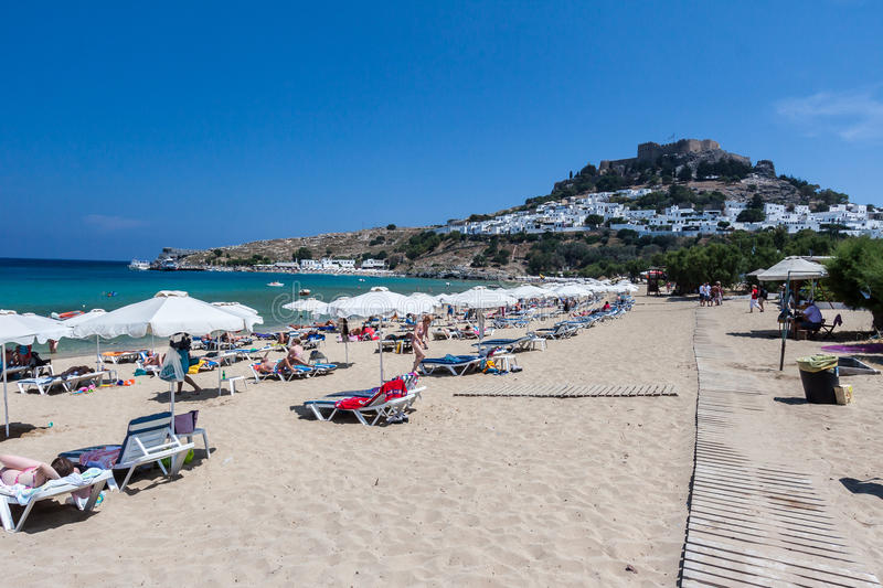 Lindos Rhodes Greece. Tourists enjoying the blue waters of the beach, the typical white greek housing of the town climbing the hill and the imposing Knights stock images