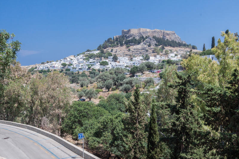 Lindos Rhodes Greece. The typical white greek housing of the town climbing the hill and the imposing Knights fortress on its top with the ruins of the ancient stock image