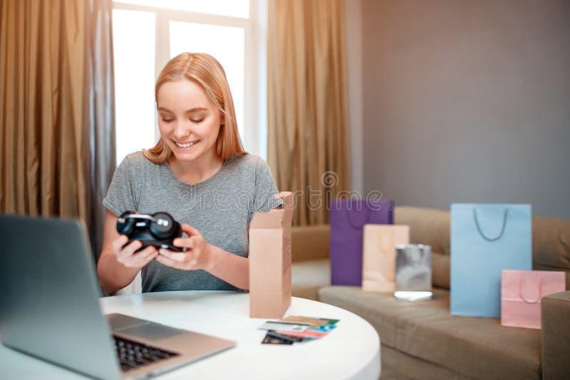 On-line ψωνίζοντας στο σπίτι Ο νέος ξανθός αγοραστής είναι ευχαριστημένος από την αγορά μόδας, που διατάζεται και που παραδίδεται στοκ φωτογραφίες με δικαίωμα ελεύθερης χρήσης