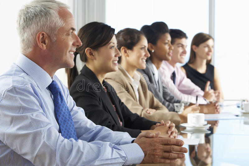 Line Of Business People Listening To Presentation Seated At Glass Boardroom Table royalty free stock images