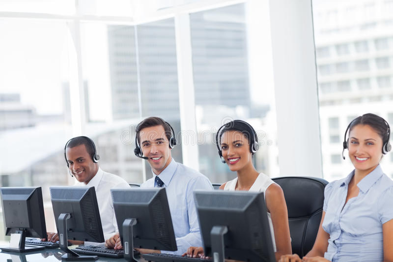 Line of call centre employees smiling. And working on computers royalty free stock image