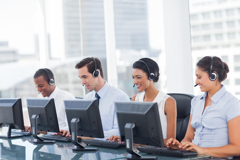 Line of call centre employees. Working on computers stock image