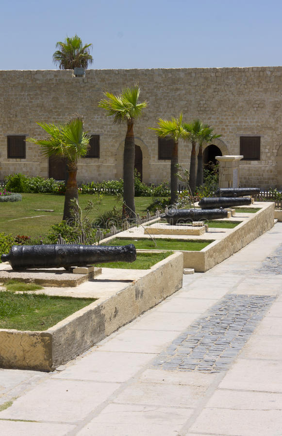Line of cannons. In the entrance yard to the Citadel of Qaitbay with the protective wall surrounding the citadel in Alexandria stock photography