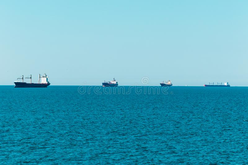 Line of cargo vessels at the horizon sailing to Hamburg. Line of cargo vessel on the horizon on their way to the port of Hamburg, seen near Cuxhaven royalty free stock photos