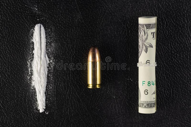 A line of cocaine powder, single bullet and dollar bill scroll on black surface stock image