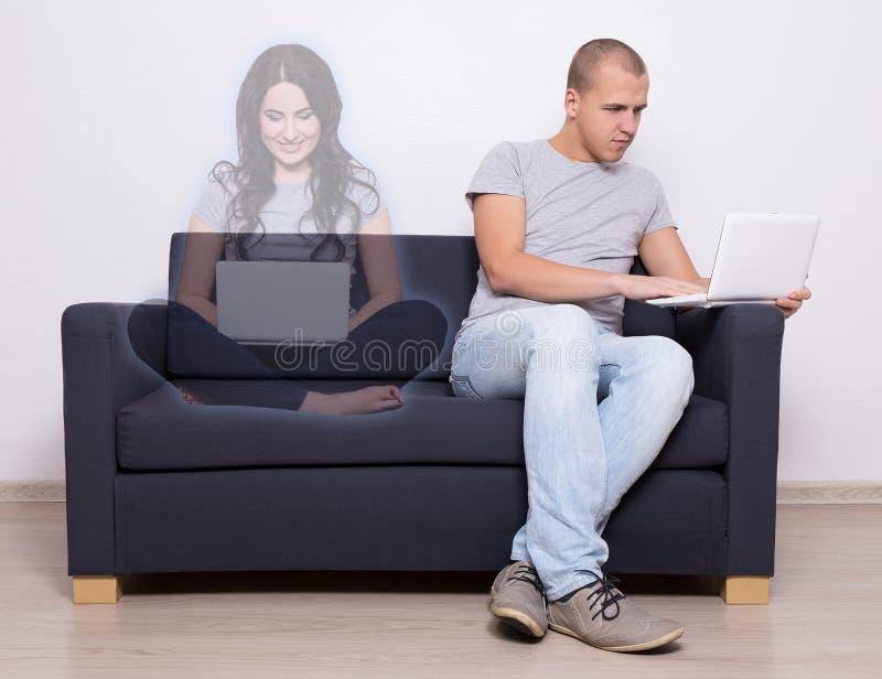 On-line-Datierungskonzept - gutaussehender Mann, der auf Sofa und chattin sitzt stockfoto