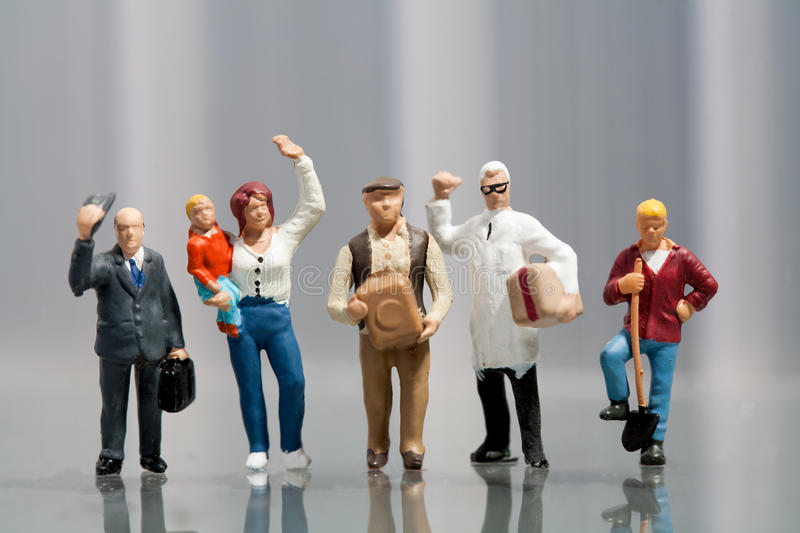 Line of diverse people in population demographics. Line of diverse tiny miniature model people in population demographics representing a cross section of the stock photography