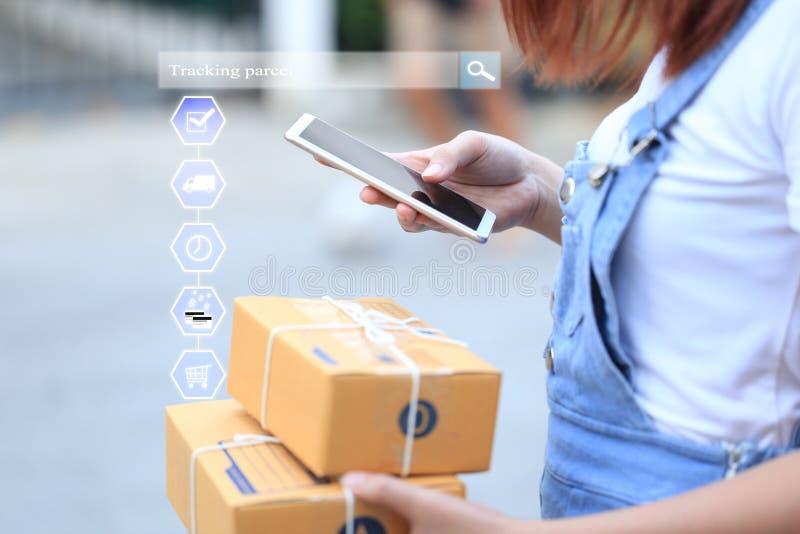 On-line-Einkaufen, Frauenhand, die intelligentes Telefon hält und online Paket aufspürt, um Status mit Hologramm, elektronischem  stockbild