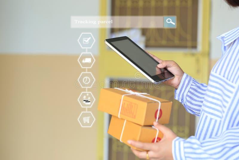 On-line-Einkaufen, Frauenhand, die intelligentes Telefon hält und online Paket aufspürt, um Status mit Hologramm, elektronischem  lizenzfreie stockbilder