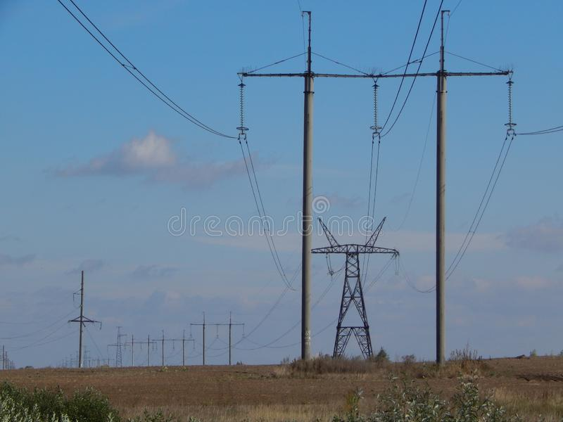The line of high-voltage electricity transmission идущая through the field. Metallic wires are suspended on posts. Tension in the tendons of royalty free stock photography