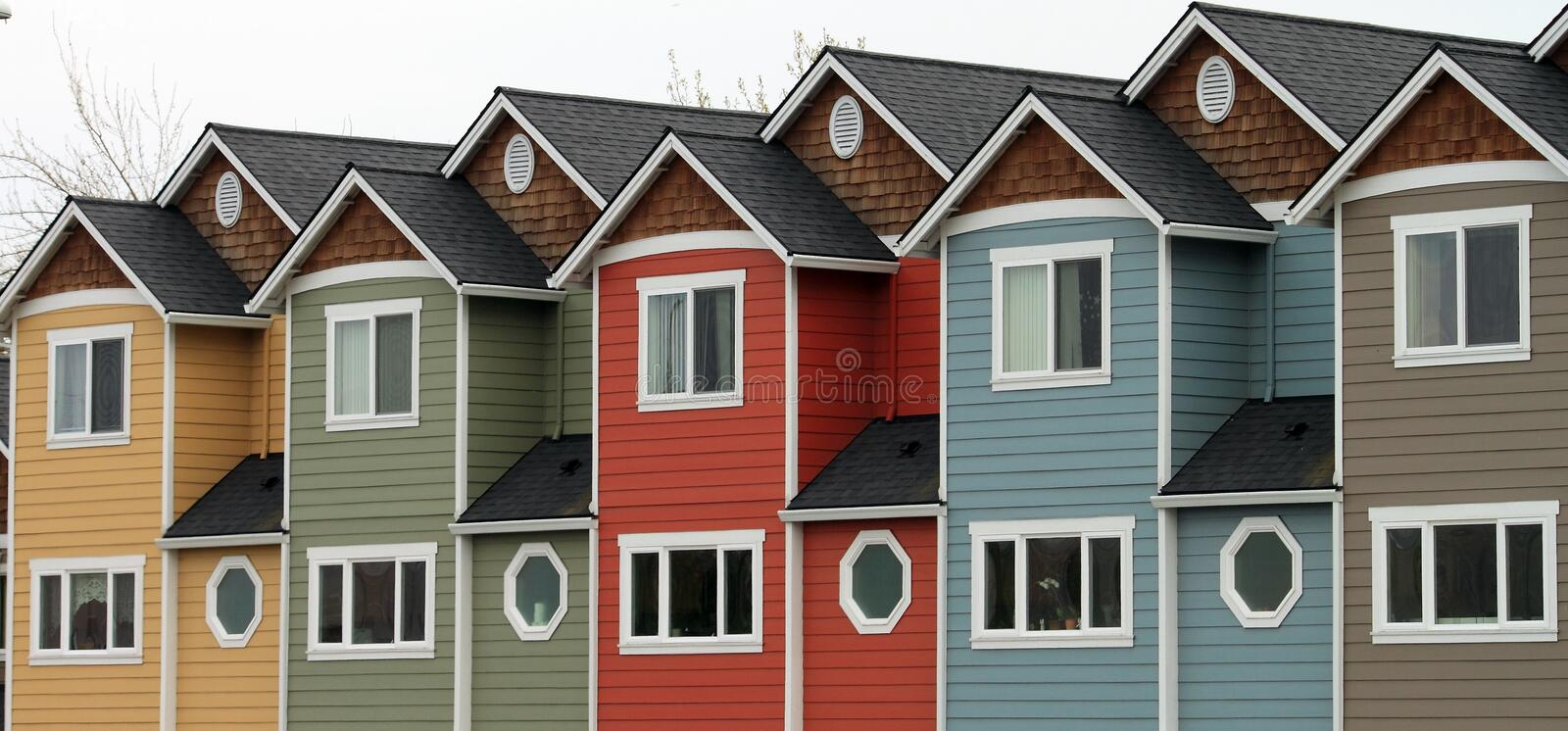 Line of Homes. A line of colorful attached identical modern homes with lots of windows