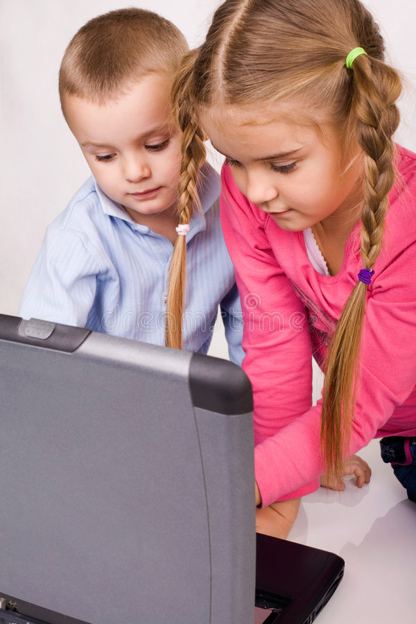 On line learning. Kids playing computer games or learning on line royalty free stock photography
