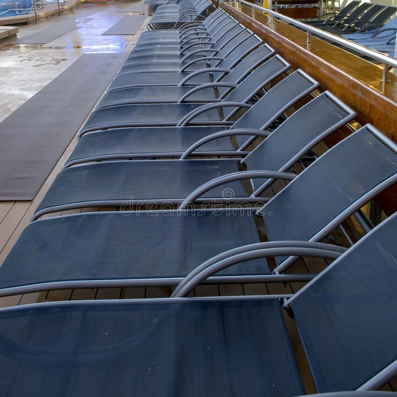 Line of lounge chairs on cruise ship stock photography