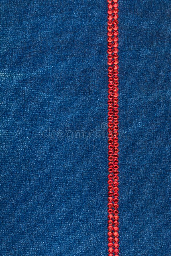 Line made of blue crystals on blue denim fabric. Luxurious, beautiful, fashionable background. stock photography