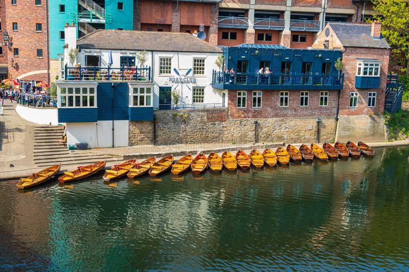Line of moored rowing boats on the banks of River Wear near a boat club in Durham, United Kingdom on a beautiful spring afternoon. Durham, United Kingdom - April stock photos