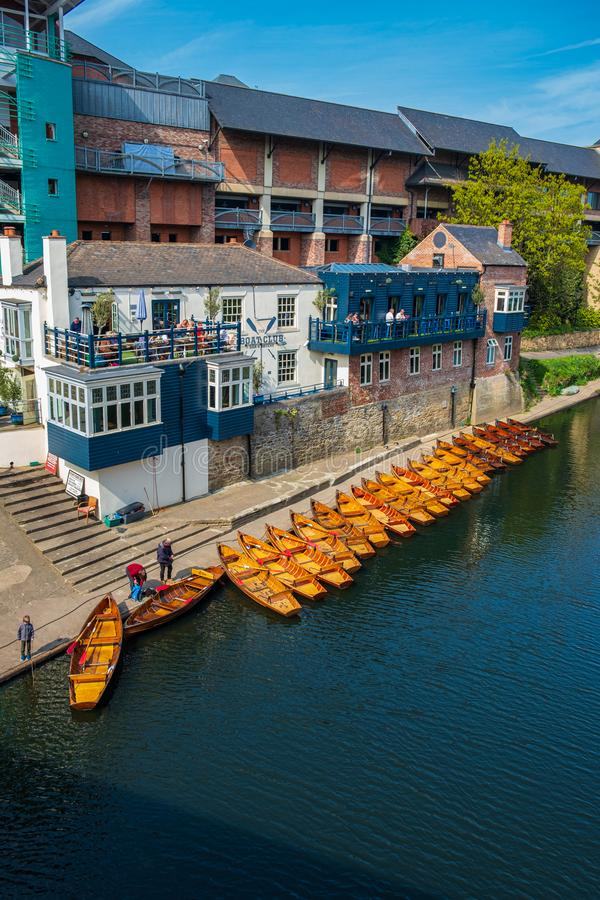 Line of moored rowing boats on the banks of River Wear near a boat club in Durham, United Kingdom on a beautiful spring afternoon. Durham, United Kingdom - April stock images