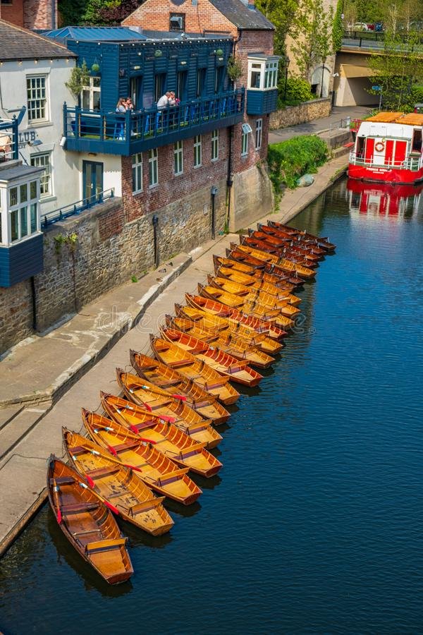 Line of moored rowing boats on the banks of River Wear near a boat club in Durham, United Kingdom on a beautiful spring afternoon. Durham, United Kingdom - April royalty free stock image